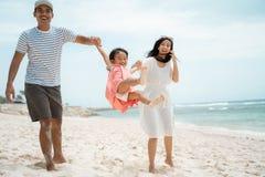Отец и мать отбрасывая маленькую девочку на пляже стоковые изображения rf