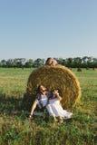 Отец и мать сидя под стогом сена, и их дочь сидя на стоге сена Стоковая Фотография RF