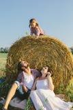 Отец и мать сидя под стогом сена, и их дочь сидя на стоге сена Стоковые Фото