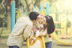 Отец и мать целуя дочь на скольжениях стоковое изображение