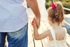 Отец и маленькая дочь держа рука об руку на заходе солнца Стоковые Фотографии RF