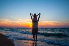 Отец и маленькая дочь на пляже на заходе солнца Стоковые Изображения