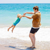 Отец и маленький мальчик малыша имея потеху на пляже Стоковое фото RF