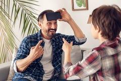 Отец и меньший сын дома сидя на софе играя головы вверх со смартфоном угадывая слово жизнерадостное стоковое изображение rf