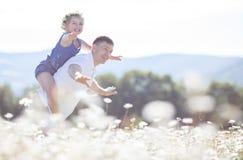 Отец и дочь в поле лета зацветая маргариток Стоковое фото RF