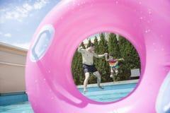 Отец и дочь держа руки и скача в бассейн, увиденный до конца раздувной розовой трубке Стоковые Изображения