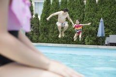 Отец и дочь держа руки и скача в бассейн Стоковые Изображения