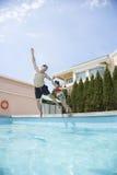 Отец и дочь держа руки и скача в бассейн Стоковое Изображение RF