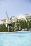 Отец и дочь держа руки и скача в бассейн Стоковые Фотографии RF