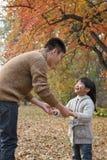 Отец и дочь держа руки, смотря один другого в парке, осень Стоковое фото RF