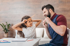Отец и дочь делая рожки и клыки из карандашей пока рисующ дома Стоковое Фото