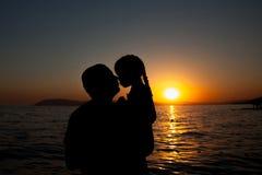 Отец и дочь играя на пляже на времени захода солнца жулик Стоковые Изображения