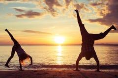 Отец и дочь играя на пляже на времени захода солнца Стоковые Фото