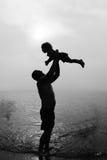 Отец и дочь играя на пляже на заходе солнца стоковая фотография rf