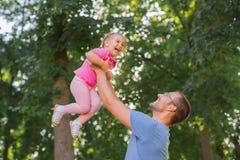 Отец и дочь играя снаружи в парке стоковые фото