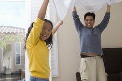 Отец и дочь играя с простыней стоковые изображения rf