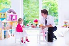 Отец и дочь играя чаепитие куклы Стоковые Изображения