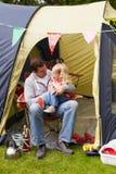 Отец и дочь наслаждаясь располагаясь лагерем праздником на месте для лагеря стоковое фото