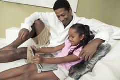 Отец и дочь на софе смотря кино на портативное DVD-плеер Стоковое Фото
