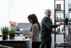Отец и дочь подготавливая еду в кухне Стоковая Фотография RF