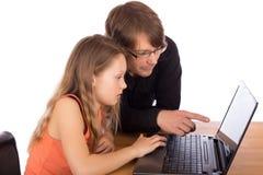 Отец и дочь работая на компьтер-книжке Стоковые Изображения