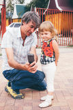Отец и дочь семьи смотря мобильный телефон Стоковые Изображения RF