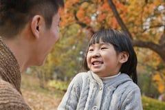 Отец и дочь смотря один другого в парке, осень Стоковое фото RF