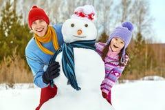 Отец и дочь с снеговиком Стоковые Фото