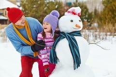 Отец и дочь с снеговиком Стоковое Изображение RF