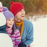 Отец и дочь с снеговиком Стоковое Фото