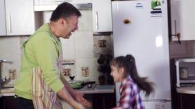 Отец и счастливая маленькая девочка с игрой темных волос в кухне сток-видео