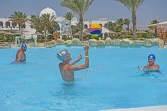 Отец и сыновьья играя воду в тропическом бассейне курорта Стоковые Изображения