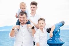 Отец и сыновьья на море Семья на платформе просмотра около монетки стоковые изображения rf