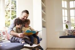 Отец и сыновьья читая рассказ дома совместно стоковое изображение