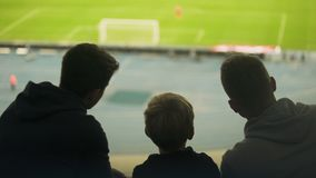 Отец и 2 сынов наблюдая футбольный матч совместно, счастливые выходные, отцовство видеоматериал