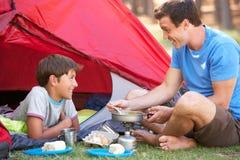 Отец и сын варя завтрак на располагаясь лагерем празднике Стоковые Изображения