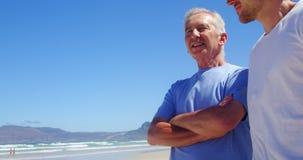 Отец и сын взаимодействуя друг с другом на пляже акции видеоматериалы
