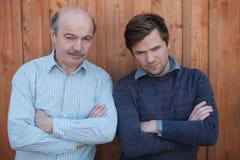 Отец и сын враждовали Они смотрят с сердитой эмоцией на камере, пересеченных оружиях Стоковая Фотография RF