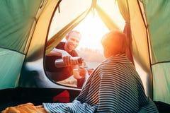 Отец и сын выпивают горячий чай в touristic шатре стоковое изображение rf