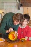 Отец и сын высекая тыкву хеллоуина на кухонном столе Стоковые Фотографии RF