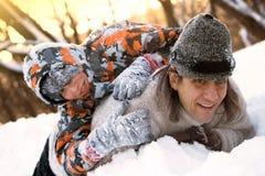 Отец и сын в зиме на холоднопрокатн и игра в снеге Стоковые Изображения