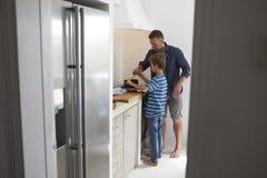 Отец и сын в кухне делая еду совместно Стоковая Фотография RF