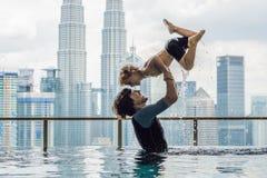 Отец и сын в открытом бассейне с видом на город в голубом s стоковая фотография