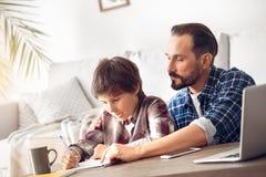 Отец и сын дома сидя на мальчике показа папы таблицы как сделать назначение стоковые изображения