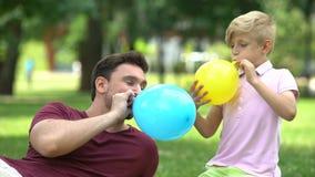 Отец и сын дуя - вверх по воздушным шарам, имеющ потеху совместно, беспечальное воссоздание видеоматериал