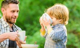 Отец и сын едят на открытом воздухе E Выпуск облигаций дня семьи небольшой ребенок мальчика с папой они любят съесть совместно стоковое фото