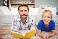 Отец и сын держа книгу лежа на поле дома Стоковая Фотография