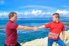 Отец и сын держа руки Стоковое Изображение RF