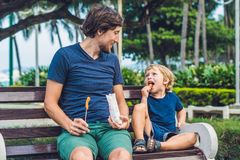 Отец и сын едят зажаренные сладкие картофели в парке еда рыб огурца принципиальной схемы цыпленка сыра бургера предпосылки глубок Стоковое Фото