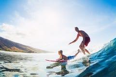 Отец и сын занимаясь серфингом, ехать волна совместно стоковые изображения rf